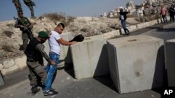 FILE - Israeli border police search a Palestinian next to newly placed concrete blocks in an East Jerusalem neighborhood, Oct. 15, 2015.