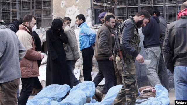 Free Syrian Army fighters and residents attempt to identify bodies found along a river, at a school used as a field hospital in Aleppo, Syria, January 29, 2013
