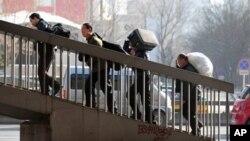 圖為去年3月2日民工扛著行李在北京車站附近走上一架天橋 (資料照片)