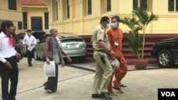 Ratt Roth Mony, wearing an orange jumpsuit and face mask, is being escorted by a national police officer after a hearing at the Supreme Court in Phnom Penh, Cambodia, July 1, 2020. (Hul Reaksmey/VOA Khmer)