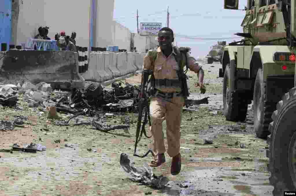 A Somali government soldier runs to take cover during crossfire after gunmen attacked a U.N. compound in Mogadishu, June 19, 2013.