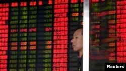 Seorang investor berdiri di depan papan monitor yang menunjukkan harga-harga saham di Shanghai, China (2/9). Bursa-bursa saham domestik China telah anjlok hampir 40 persen sejak pertengahan Juni.