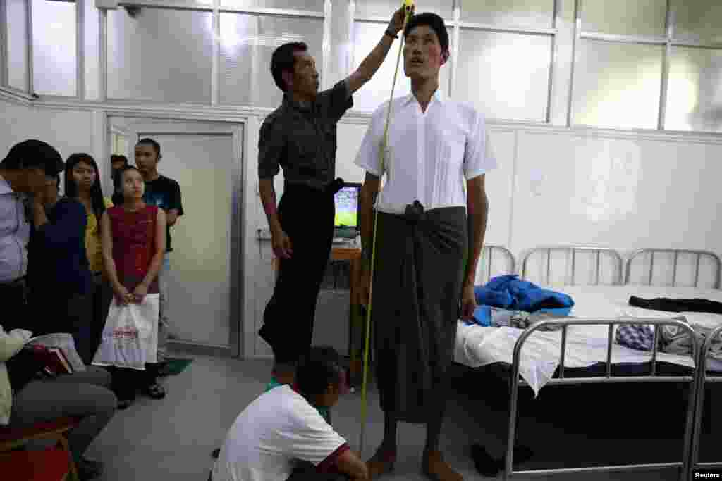 Win Zaw Oo, 36, has his height measured during a medical check-up at a clinic in Rangoon. Win Zaw Oo, who stands at 7 feet 5 inches tall, is Burma's tallest man, according to the medical team.