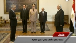 This screen grab from state television shows Egypt's interim President Adly Mansour (R) swearing in Ahmed Galal (L) as finance minister in Cairo, July 16, 2013.