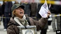 中國的一位訪民手持上訪信下跪伸冤(資料照片)