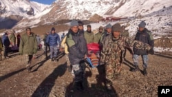 In this photo provided by the Nepalese army, soldiers carry an avalanche victim to an airlift transfer point in Thorong La pass area, Nepal, Oct. 15, 2014.