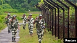 FILE - Female personnel of India's Border Security Force patrol along the fencing of the India-Bangladesh international border ahead of India's Independence Day celebrations, at Dhanpur village in India's northeastern state of Tripura, August 2014.