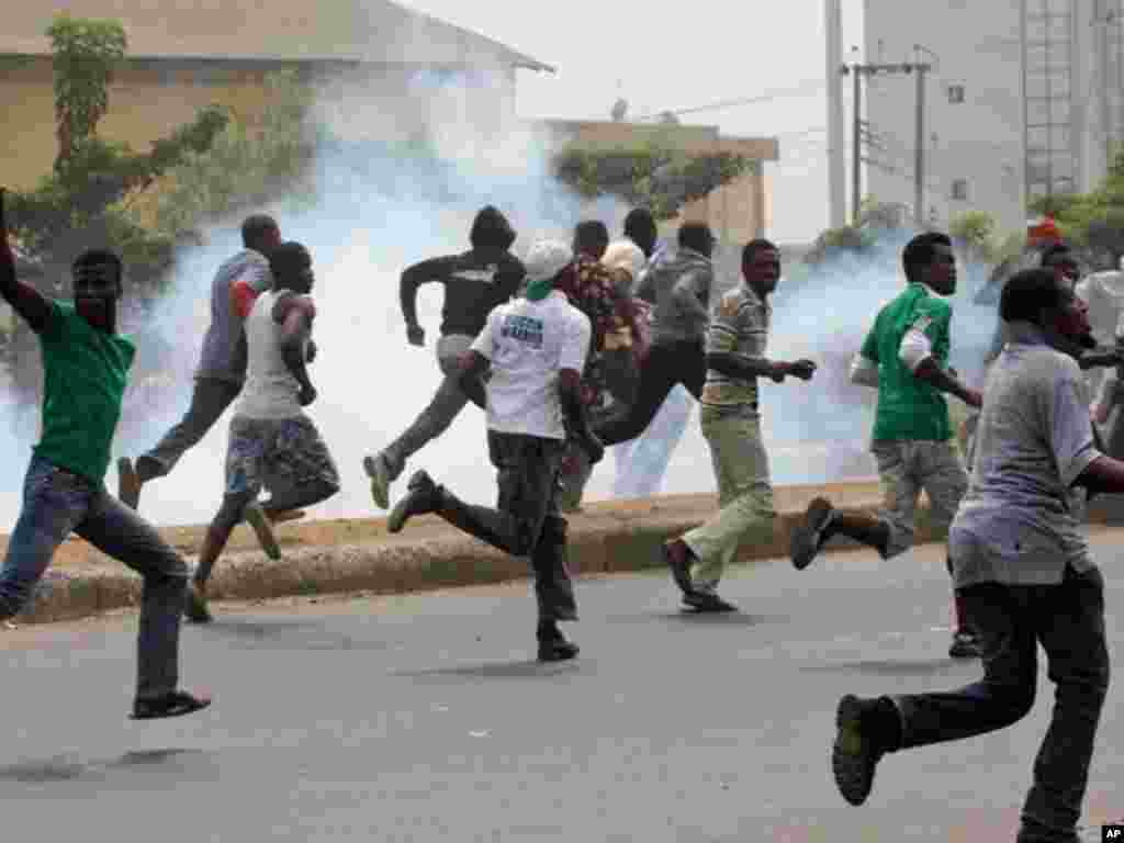 Protesters run away from tear gas fired by police officers during a demonstration against spiraling fuel prices in Lagos, Nigeria, on January 16, 2012. (AP)
