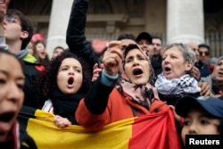 People sing as they gather around a makeshift memorial at the Place de la Bourse (Beursplein) in Brussels on March 23, 2016, a day after blasts hit the Belgian capital.