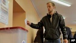 Seorang warga Latvia memasukkan surat suaranya ke dalam kotak suara di sebuah TPS di Riga, Latvia (Foto: dok).