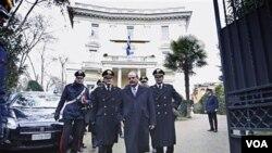 Duta besar Yunani untuk Italia, Michael E. Cambanis (kedua dari kanan), didampingi petugas keamanan Italia, berjalan keluar dari Kedutaan Besar.
