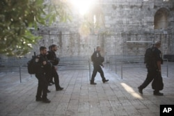 Israeli police officers walk outside the Al-Aqsa Mosque compound in Jerusalem's Old City, July 25, 2017.