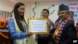 Nepalese woman climber Lhakpa Sherpa, left, is honored with an honorary certificate in Kathmandu, Nepal, Wednesday, May 23, 2018. (AP Photo/Niranjan Shrestha)