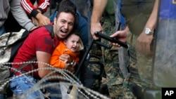 Người nhập cư bị kẹt giữa cảnh sát chống bạo động Macedonia và di dân trong một cuộc đụng độ gần ga xe lửa biên giới của thành phố Idomeni, miền bắc Hy Lạp, 21/8/2015.