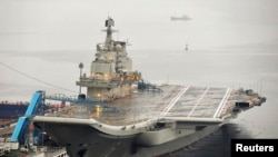 FILE - China's first aircraft carrier, renovated from an old aircraft carrier bought from Ukraine, is shown docked in Dalian, Liaoning province in 2012. A senior U.S. Navy delegation toured the ship this week.