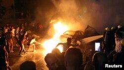 دھماکے کے بعد گاڑیوں میں لگنے والی آگ کو مقامی افراد بجھانے کی کوشش کر رہے ہیں۔