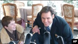 Mr. Popper (Jim Carrey) and his son Billy (Maxwell Perry Cotton) enjoy the penguins.