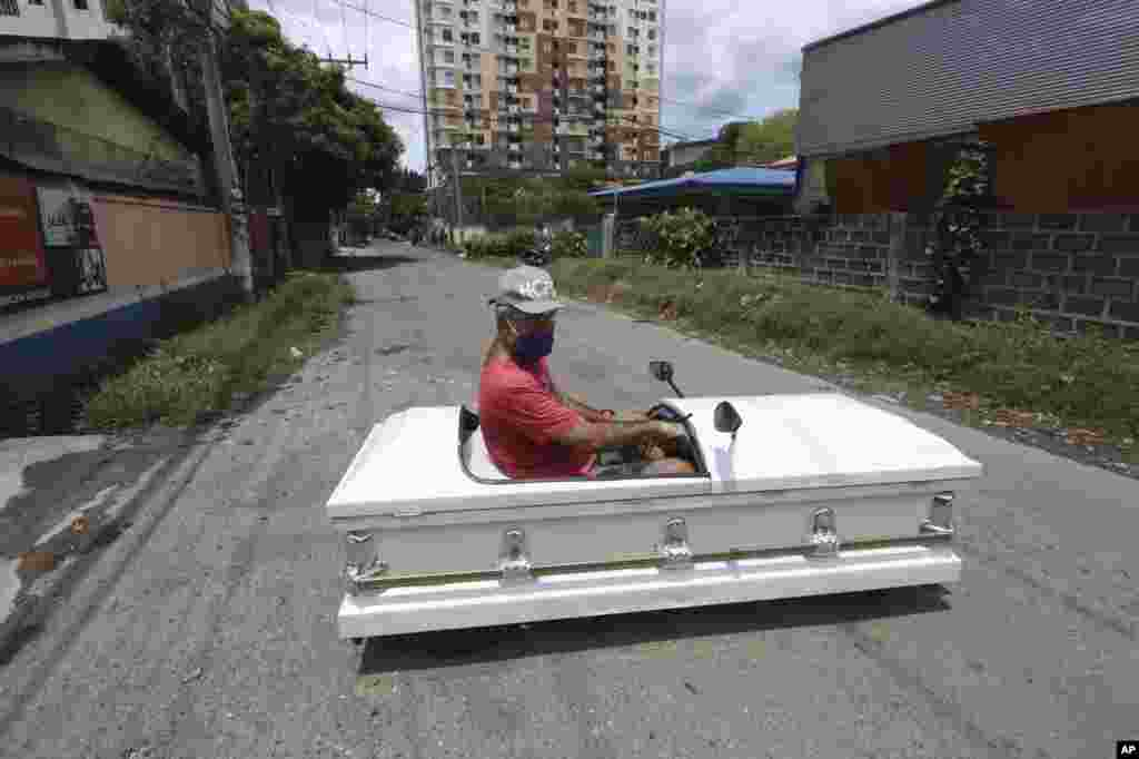 Gabriel Berendo, a businessman and car enthusiast, drives a casket converted into a car in Cebu city, central Philippines, as he goes around streets to remind residents to stay at home as lockdown measures to prevent the spread of the COVIA-19.