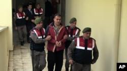 Des policiers turcs escortent des passeurs syriens Muwafaka Alabash (devant) et Asem Alfrhad (derrière) pour leur procès à Bodrum, Turquie, le vendredi 4 Mars 2016. (AP Photo)