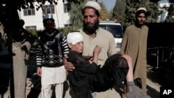 مرد افغان پسرک مجروحی را پس از انفجار دوبمب در منطقه اچین در جلال آباد در پاییز گذشته به بیمارستان می برد