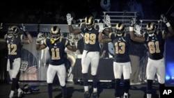 "Stedman Bailey (12), Tavon Austin (11), Jared Cook, (89) Chris Givens (13) and Kenny Britt (81) levantan sus brazos como en ""Manos arriba, no disparen"", el lema en Ferguson."