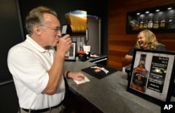Scott Schwar, left, of Oak Park, Illinois, orders the first cocktail from Stacy Clark at the new Jim Beam Bourbon Bar located on the grounds of the Jim Beam Distillery, Sept. 14, 2016, in Clermont, Kentucky.