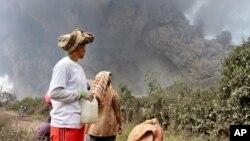 Warga desa setempat mengamati gunung Sinabung saat kembali mengeluarkan awan tebal di Namantaram, Sumatera Utara, Indonesia (1/2).