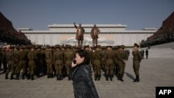 FILE - A woman talks on a mobile phone as Korean People's Army soldiers gather for a memorial tribute before the statues of late North Korean leaders Kim Il Sung and Kim Jong Il, on Mansu hill in Pyongyang, North Korea, April 15, 2019.