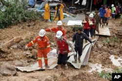 Members of a Myanmar rescue team carry a body at a landslide-hit area in Paung township, Mon State, Myanmar, Aug. 10, 2019.