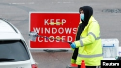 A NHS worker passes a COVID-19 test kit to a driver at a mobile test center, amid the coronavirus outbreak, in Broxbourne, Hertfordshire, Britain, Feb. 2, 2021.