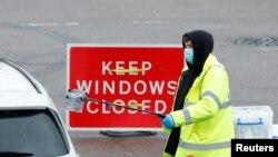 Seorang petugas NHS memberikan alat tes COVID-19 ke seorang pengemudi di pusat tes lantatur di tengah merebaknya wabah virus corona di Broxbourne, Hertfordshire, Inggris, 2 Februari 2021.