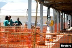 FILE - A health worker dressed in a protective suit talks to medical staff at the newly constructed MSF (Doctors Without Borders) Ebola treatment center in Goma, Democratic Republic of Congo, Aug. 4, 2019.