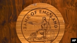 A wooden carving of the Bank of England logo is seen on a desk during a news conference by Bank of England governor Mark Carney at the Bank of England in London, Britain July 5, 2016. Carney says some of the risks predicted to the economy before the…
