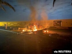 Burning debris is seen on a road near the Baghdad International Airport that Iraqi paramilitary groups said was caused by three rockets hitting the airport, Jan. 3, 2020. (Iraqi Security Cell/Reuters)