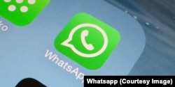 A Whatsapp icon is seen on a smartphone.