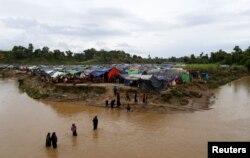 FILE - Rohingya refugees cross a stream to reach their temporary shelters at No Man's Land between the Bangladesh-Myanmar border, at Cox's Bazar, Bangladesh, Sept. 9, 2017.