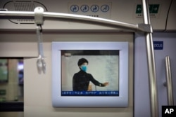 A public service announcement that encourages people to wear face masks plays on a subway train during the morning rush hour in Beijing, Feb. 3, 2020.