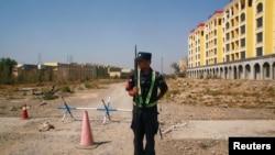 资料照片:中国警察在新疆伊宁一处官方所说的职业教培中心附近的路口站岗。(2018年9月4日)