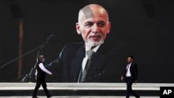 FILE - In this Aug. 14, 2021 file photo, a mural of Afghan President Ashraf Ghani hangs at Hamid Karzai International Airport, in Kabul, Afghanistan.