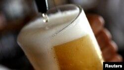 ARSIP – Tampak bir dituangkan ke gelas di sebuah bar di London, Inggris, 27 Juni 2018 (foto: Reuters/Peter Nicholls/Foto Arsip
