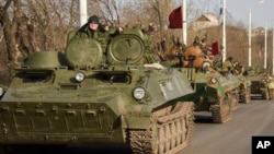 FILE - Pro-Russia rebels are seen driving in a convoy of armored vehicles and tanks in Stakhanov, eastern Ukraine, April 24, 2015.