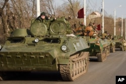 FILE - Pro-Russia rebels are seen driving in a convoy in Stakhanov, eastern Ukraine, April 24, 2015. Meeting Tuesday in Sochi, Russian President Vladimir Putin and German Chancellor Angela Merkel continued to disagree on the causes of the conflict in eastern Ukraine.