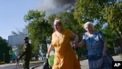 Phụ nữ vội vã chạy trên đường phố sau khi xảy ra bắn phá trong thị trấn Donetsk, phía đông Ukraine, 27/8/14 Chính quyền Tổng thống Obama cáo buộc Nga dàn dựng một chiến dịch quân sự mới ở Ukraine, giúp lực lượng nổi dậy mở rộng cuộc chiến ở miền đông nước, đưa xe tăng, bệ phóng tên lửa và xe bọc thép đến các nơi khác