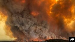 FILE - Wildfires rage under plumes of smoke in Bairnsdale, Australia, Dec. 30, 2019.