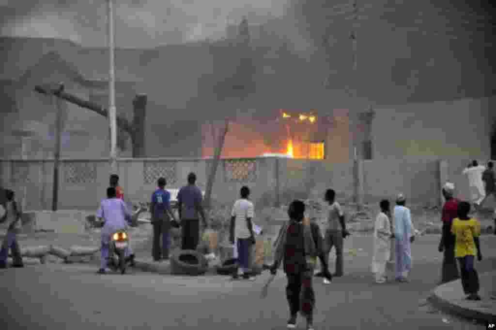 People watch as smoke rises from the police headquarters after it was hit by a blast in Nigeria's northern city of Kano January 20, 2012.