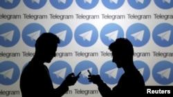 两名使用手机的男子站在俄罗斯加密通信平台Telegram的标志前。(2015年11月18日)