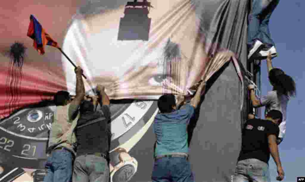 Lebanese of Armenian descent carry an Armenian flag as they tear up a poster showing Turkish Prime Minister Recep Tayyip Erdogan during a protest against his visit, in Beirut's Martyrs' Square, Lebanon, Thursday, Nov. 25, 2010. Armenians accuse Turkey of