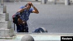 Một người đàn ông giải nhiệt tại đài phun nước ở trung tâm của Rome, Ý, ngày 25 tháng 6, 2019