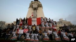 """Demonstrators hold posters with a message that reads in Spanish; """"Reject the Narco State, reject Keiko,"""" during a protest against presidential candidate Keiko Fujimori, at Plaza San Martin in downtown Lima, Peru, May 31, 2016."""