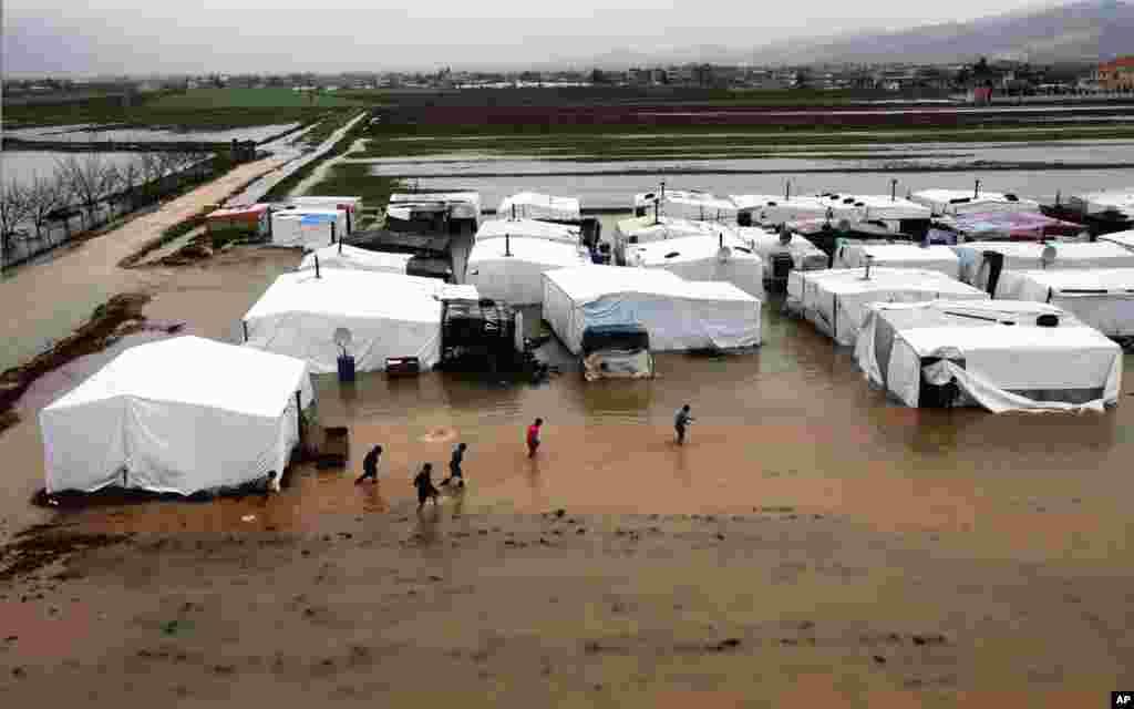 叙利亚难民通过和叙利亚接壤的黎巴嫩边境地区阿勒法奥尔一处被水淹的一个暂时难民营地。